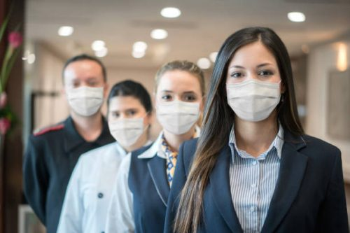 Group of Latin American hotel workers in a row wearing facemask during the COVID-19 pandemic and looking at the camera